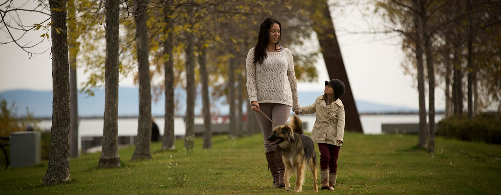 mother and daughter walking with dog